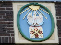 """Plaque above the first storey of Joost R. Ritman's house on Bloemgracht. Inside the green ouroborous (serpent biting its tail) a pelican sits on a crescent moon and prepares to give blood from its breast to feed its young. Below that the letters RC (Red Cross) and AO (Alpha and Omega) on four red roses, separated by a gold cross. Above the main entrance the motto """"In de Pelikaan""""."""