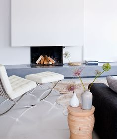 Lovely home. White. Fireplace. White Barcelona Chair!
