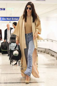 Jenner goes casual chic for her flight from London to Los Angeles wearing a tan bodysuit and RE/DONE | Levi's The Elsa jean topped with a camel duster jacket.