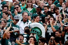 Michigan State basketball coach Tom Izzo cheers with the Michigan State student section after a defensive touchdown during the Spartans' 21-6 win over South Florida at Spartan Stadium in East Lansing on Saturday. Izzo promised students he would spend part of the game in the student section if they left the stadium during a rain delay after they refused to do so when asked by officials. (Mike Mulholland | MLive.com)