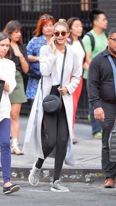 Gigi looked so stylish in a grey coat, white tee, black leggings, circle cross body bag, and sneakers.