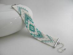 Bracelet fait à la main sur un métier à tisser. 19 rangs, 3 couleurs. Motif aztèque. Couleurs: blanc nacré, argenté et bleu canard. Embouts, anneaux et fermoir mousqueton - 18804307