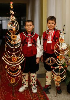 """Survakane (""""Сурвакане"""") - Children and in some areas only boys gather to walk from door to door, going around the village, and giving blessings to the houses, householders, families and even pets, to wish everybody health and welfare throughout the New Year. In their hands they hold beautiful, decorated with yarn and dried fruits, cornel branches, called survachki (""""сурвачки""""). The children would say a blessing while gently patting the back of everyone in the house with the survachka."""