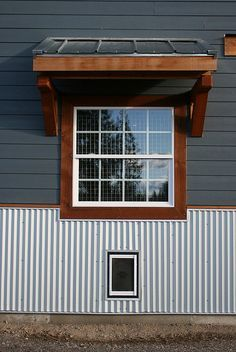 Love the metal, the gray with wood and overhang! Laundry window, overhang and dog door by Moosicorn, via Flickr