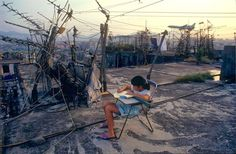 A girl does her homework on a rooftop in the Kowloon Walled City (KWC), which was a densely populated settlement in Kowloon City, Hong Kong UrbanHell Hong Kong, Kowloon Walled City, British Journal Of Photography, Candid Photography, High Rise Building, World Images, Lost City, Slums, Historical Pictures