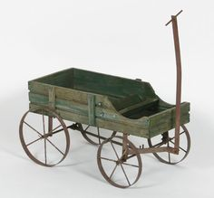 """Primitive child\'s wagon with iron wheels, metal framework and handle, and traces of original paint.  Body: 13\""""H x 23\""""W x 11\""""D.  Good condition with wear to wood and metal surfaces, structurally sound."""