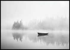 Poster with black and white photography, a beautiful lake with fog over it and an empty boat. www,desenio.com