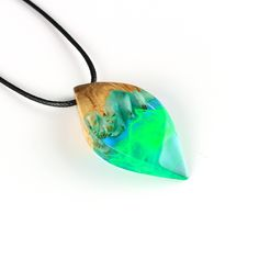 This necklace is handcarved from transparent resin and is combined with a piece of exotic burl wood. Made to look as if there is a tiny northern light inside, this piece of nature inspired jewelry would make a great gift for anyone who loves nature. The resin has glass like properties and is polished to a high gloss finish, making it completely transparent. The pendant is unique, and it is impossible to make another piece exactly like it. The necklace comes presented in a black modern…