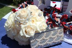 Imprint Affair uses the beautiful white roses of the bridal bouquet to display the bride's gorgeous pearl purse, bracelet and engagement ring atop the red, white, and blue sweetheart table. Bouquet designed by Imprint Affair and accessories styled by IMPRINT Lifestyle Concierge.
