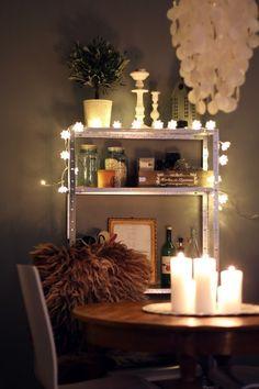 Drape lights over a bookshelf.