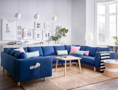 Un salón luminoso con un gran sofá en U para nueve personas cubierto con una tela azul oscuro. Combinado con una mesa de centro de chapa de fresno y una mesa redonda con bandeja de ratán con espacio para guardar cosas.