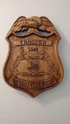 "Personalized Michigan State Trooper Police Badge V Carved Wooden Sign. This is a great gift for your Wife, Husband, Fellow Worker, Relative, Etc.. who is in law enforcement. We can make custom signs as well. Approx size is 11"" wide x 16"" high. Comes with Picture hanger on the back. These are made on our CNC machine and takes about 4 hours of machine time from start to finish."