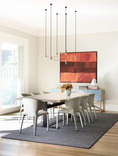 Gorgeous lighting and artwork in this dining space! #lifebetterwithart