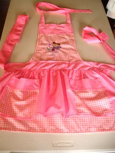 Pink Little Girl Layered Apron.   A cute fairy is embroidered on top portion.   Checked pink/white are part of the layer.