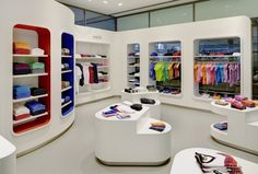 Trigema store by Heikaus, Stuttgart, Germany / Germany's largest manufacturer of sports & leisure clothing is changing its outer appearance. Clear segmentation in modern & high-quality furniture creates a comfortable sales atmosphere. The wide-open façade & generous view through the shop windows have an inviting effect. The individual product groups are emphasized in color. The sporty textiles are skilfully presented on high-quality goods presenters in rounded wall niches