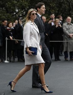 Ivanka Trump wears her own label's shoes and purse as she walks alongside her husband, Sen...