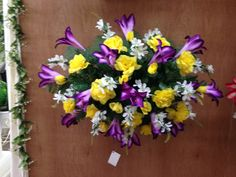 Spring/Summer silk cemetery tomb topper using purple lilies, yellow roses with white filler flowers. 2015