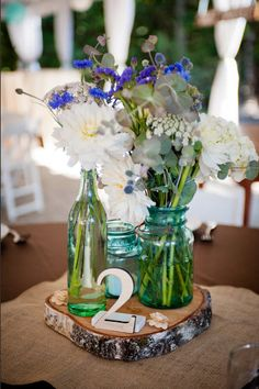 Rustic centerpiece, colored bottles and log stand -- lovely!