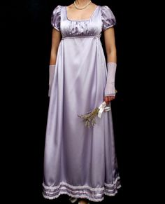This is a very feminine regency ballgown made from a fine quality lilac soft satin material. Regency puffs sleeves to the bodice styled with round neckline. Ruching to the front bodice above the empire waistline. Beautiful triple layers of pale pink satin ribbon and lace adorn the lower hem of the dress. Finished with back zip closure. A very desirable gown in mint condition for that special Regency Ball.  Modelled with accessories which are not included in the sale  Makers label: No label…