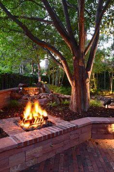 could be under the honeylocust by french doors, to give it a covered, sheltered feel - the underlit branches would be nice also.  But it would be more ornamental than this large fire pit, not primarily for warmth, just a place for a few people to sit.  it might double as one of the seat rocks, around which we could also assemble chairs when it was lit.