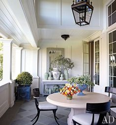 Suzanne Rheinstein--The living room terrace holds a limestone-top console and antique Chinese ginger jars from Rheinstein's popular Los Angeles shop, Hollyhock; the table and chairs are by Michael Taylor.