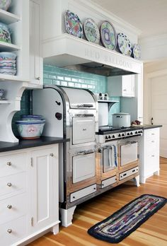 pretty kitchen.....love that stove and the splash of blue tile.