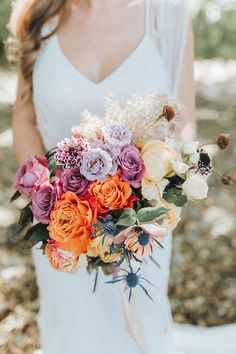 Purple Wedding Flowers Bright multicolour boho wedding bouquet featuring orange, pink, purple and yellow roses, blue thistle and swan feather Boho Wedding Bouquet, Spring Wedding Bouquets, Floral Wedding, Trendy Wedding, Unique Weddings, Wedding Dresses, Orange And Pink Wedding, Orange Wedding Flowers, Orange Pink