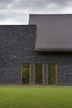 Lage-energiewoning met bureau in Aalter (hparchitect, Aalter). De donkere, gesmoorde Hectic stenen met hun ruwe textuur en vele kleurverschillen brengen variatie in de gevel. Samen met de blauw gesmoorde Plato tegelpannen creëren ze een strak en robuust volume. Hoewel de gesmoorde pannen genuanceerd zijn, zijn ze toch vrij uniform van kleur. De keuze voor de Plato pannen hielp om een zo vlak mogelijk dak te creëren. Modern Architecture House, Architecture Design, Brick Detail, Types Of Houses, Wall Treatments, Bungalow, Building A House, House Plans, Interior Decorating
