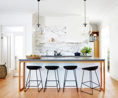 Stools at a marble kitchen island bench