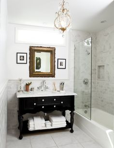 Tile wainscot on wall, furniture type vanity piece, wall mounted faucet, frameless glass panel, transom window above mirror.