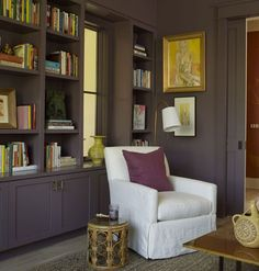 White linen upholstered furniture pops against the all-eggplant den (Like the color? It's Jamaican Java by Lord and Evans). Pops of bright yellow seen in the artwork accent the space.