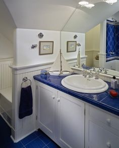 Beautiful bright blue tile with bright white cabinets.