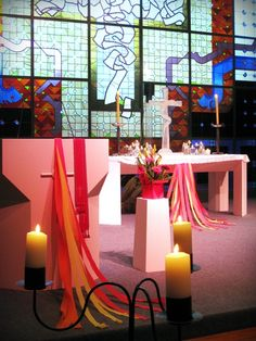 Simple and cheap decorations for Pentecost. Tealights on upturned glasses and jars on the altar!