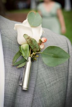 Ben's boutonniere is made up of a white rose and hypericum berries. It is placed in a shotgun shell!