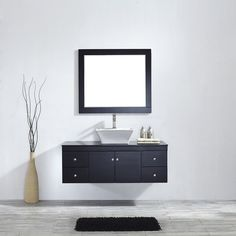 This unique piece attaches seamlessly to the wall, giving the illusion of being suspended in mid-air. The white vessel sink adds a touch of drama and contrast floating on tempered-glass countertop.While the framed mirror completes.