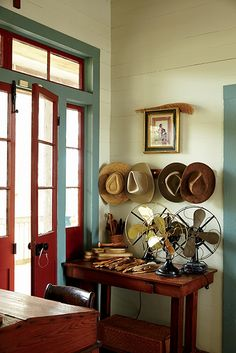 Hats and antique fans await just inside the front door for easy access. #SouthernHomes #creolecottage #gardenandgun Photo Credit: Brie Williams.