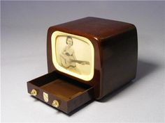 """A rare vintage Gantoy bakelite musical television 1950's  Features an animated screen with a lady playing the guitar  Small drawer with two small handles and original """"Gantoy"""" label  Musical winder to back  Drawer slides open which starts the musical mechanism, lady moves and plays guitar to the music"""