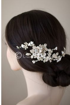 A sophisticated wedding hair clip of matte gold flowers, rhinestone jewels, pearl encrusted leaves and floating pearls. It is about 6.75 inches long and 3 inches wide, on an alligator style pinch clip