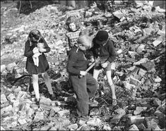 German children playing amid a massive pile of war rubble find an intact hand grenade.