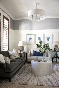 interiors by alice lane home collection | living room, wood blinds, white paneling, white wainscoting, silver metallic wallpaper, navy botanical art, taupe glass lamp, gray velvet sofa, linen settee, navy chevron pillow, john robshaw, aspen branches, round concrete coffee table, thom filicia, crank table