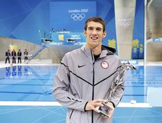 Michael Phelps poses with a trophy after receiving special recognition from FINA.