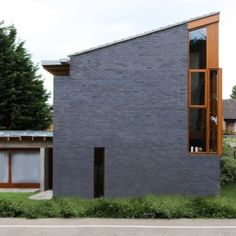 Esher House by Groves Natcheva Architects  pairs blue brickwork with red wood