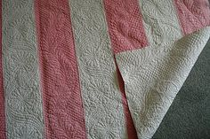 """Durham Strippy Quilt. """"Durham strippies had quilting designs which followed the strips, with border motifs being used up each strip. These strippy quilts were economical to make in fabric, easy to seam together and also easy to mark in the frame. These were the everyday quilts, although this example is especially finely worked and was a wedding gift. Seen here are a running feather pattern and a scroll and daisy pattern.""""--Pippa Moss"""