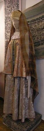Костюм просватанной невесты. XVIII в. (по образцу костюма невесты на картине М. Шибанова «Празднество свадебного договора», 1777 г.) Крестьянский девичий головной убор – «лента»; Покрывало – «фата канаватная»; Шейное украшение; Рубаха-«долгоруковка»; Сарафан косоклинный распашной; Душегрея