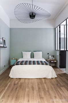 Chambre aux murs couleur vert menthe où trône une superbe suspension vertigo