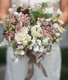 {Sweet & Romantic Bouquet With White Tulips, Pink Andromeda, White Andromeda, Lavender Sweet Pea, White Sweet Pea, & Mixed Foliage Tied Together With A Satin Mauve Ribbon}