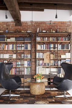 Old Fire Station Turned into Dashing Modern Industrial Loft in Montreal   living room with bookshelves + brick wall