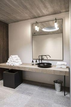 salle de bains moderne en granit avec un grand miroir et évier rond en noir