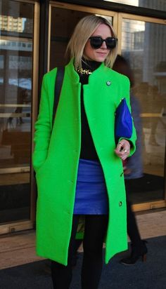 Shop this look on Lookastic:  https://lookastic.com/women/looks/coat-turtleneck-mini-skirt-clutch-sunglasses-necklace-tights/4574  — Black Sunglasses  — Gold Necklace  — Black Turtleneck  — Blue Leather Clutch  — Blue Leather Mini Skirt  — Green Coat  — Black Wool Tights