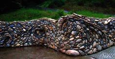 This took my breath away! A river rock garden wall. How beautiful and different! Half retaining wall and half sculpture, this river rock garden wall ensures the beauty of this outdoor space doesn't end at the edge of the garden.